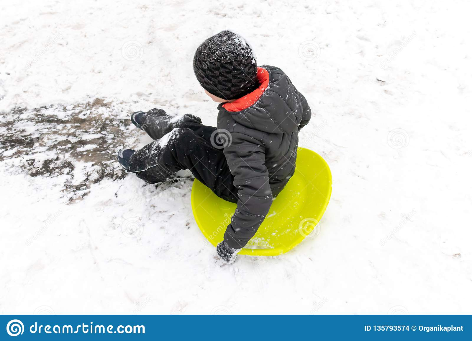 A boy of seven years old rides the slide , down the hill on green ice sled. Concept of winter activities, recreation and children
