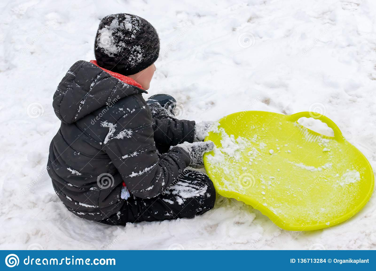 A boy of seven years old sitting on the snow and a green plastic saucer sled lying near him. Concept of winter activities,