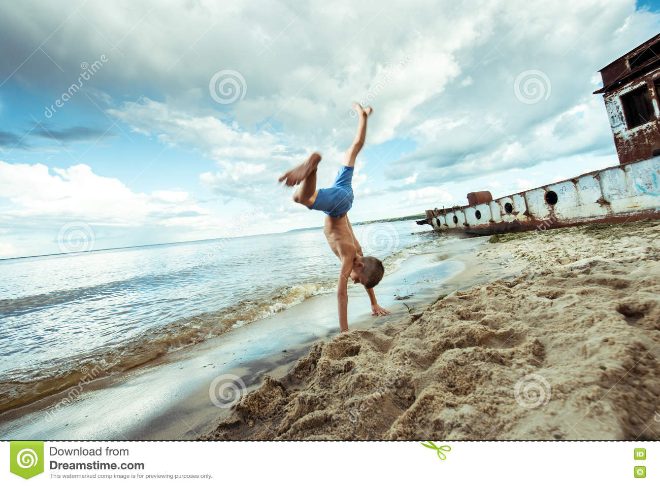 573906324 Boy Shorts Is Happy Jumps And Flips On The Beach Stock Image - Image ...