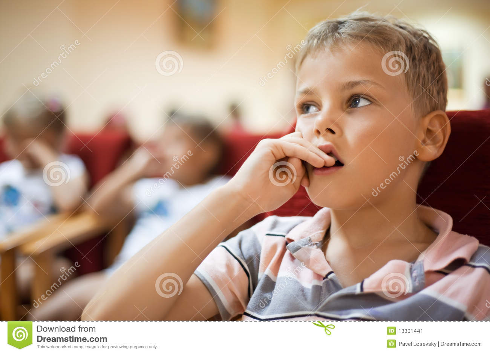 Boy sitting in cinema armchair