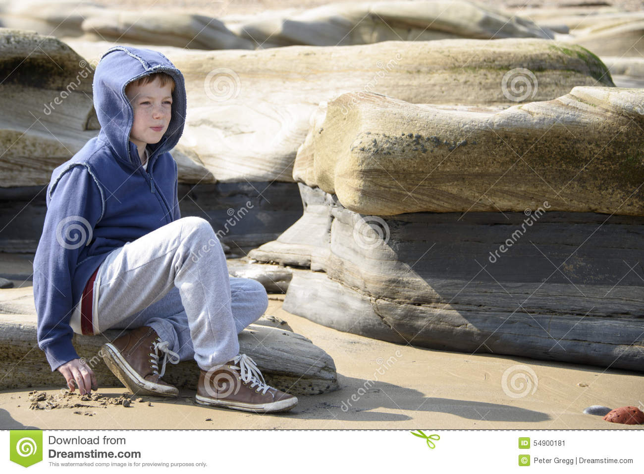 Boy sitting on rocks