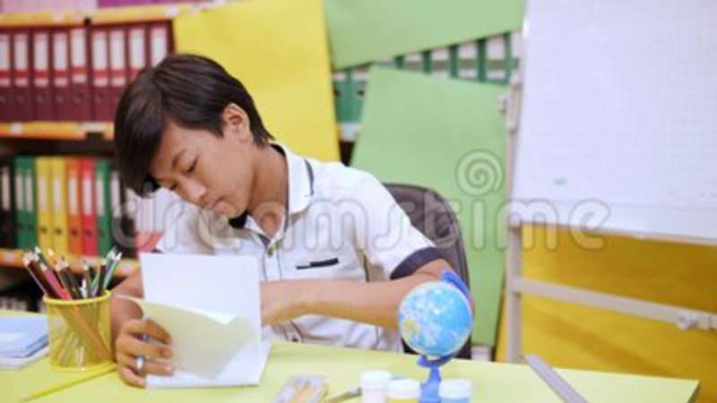 The Boy Is Sitting At The Table And Fingering The Pages Of The Notebook  Stock Video - Video of textbook, education: 123346663