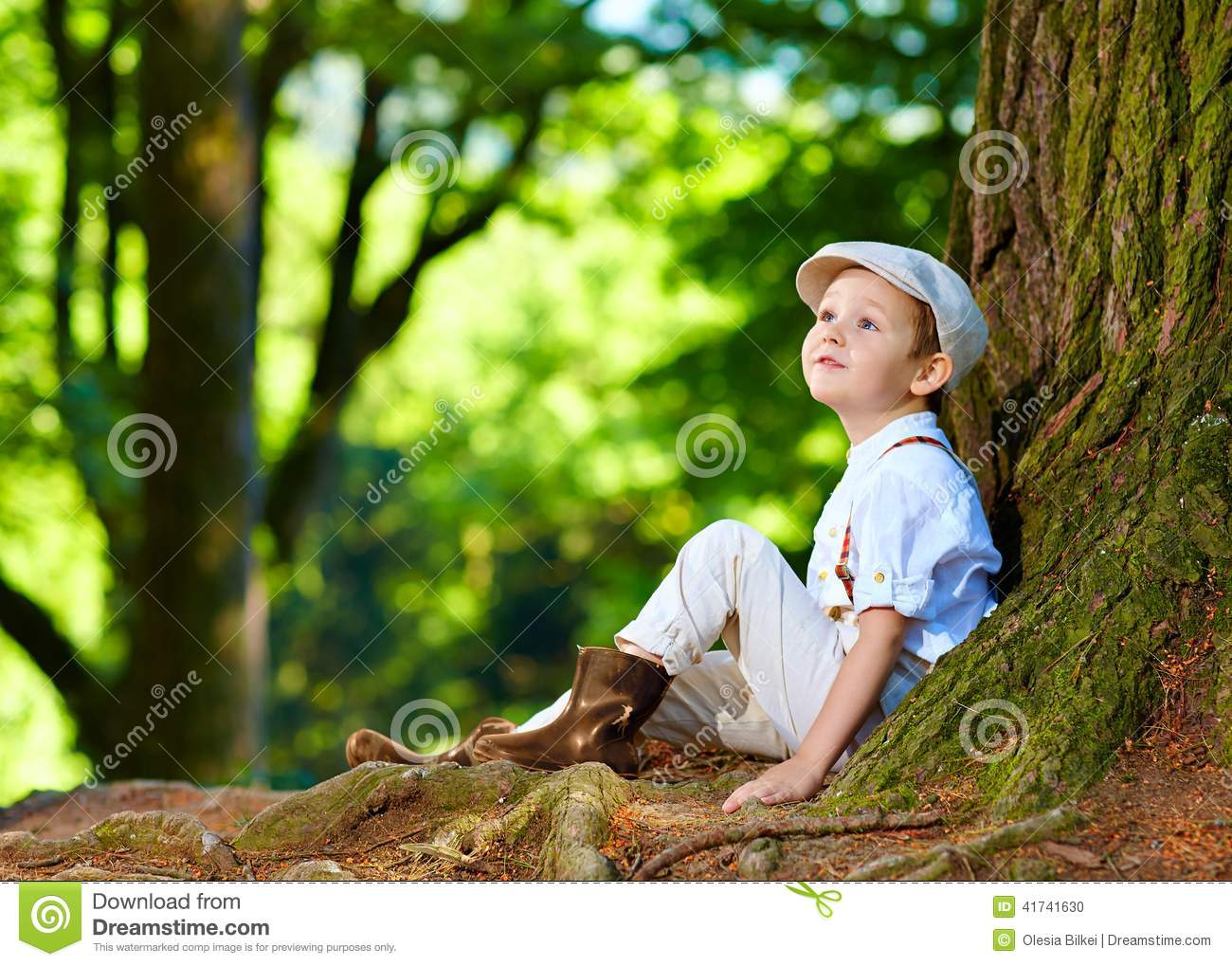 Boy Sitting Under An Old Tree In The Forest Stock Photo