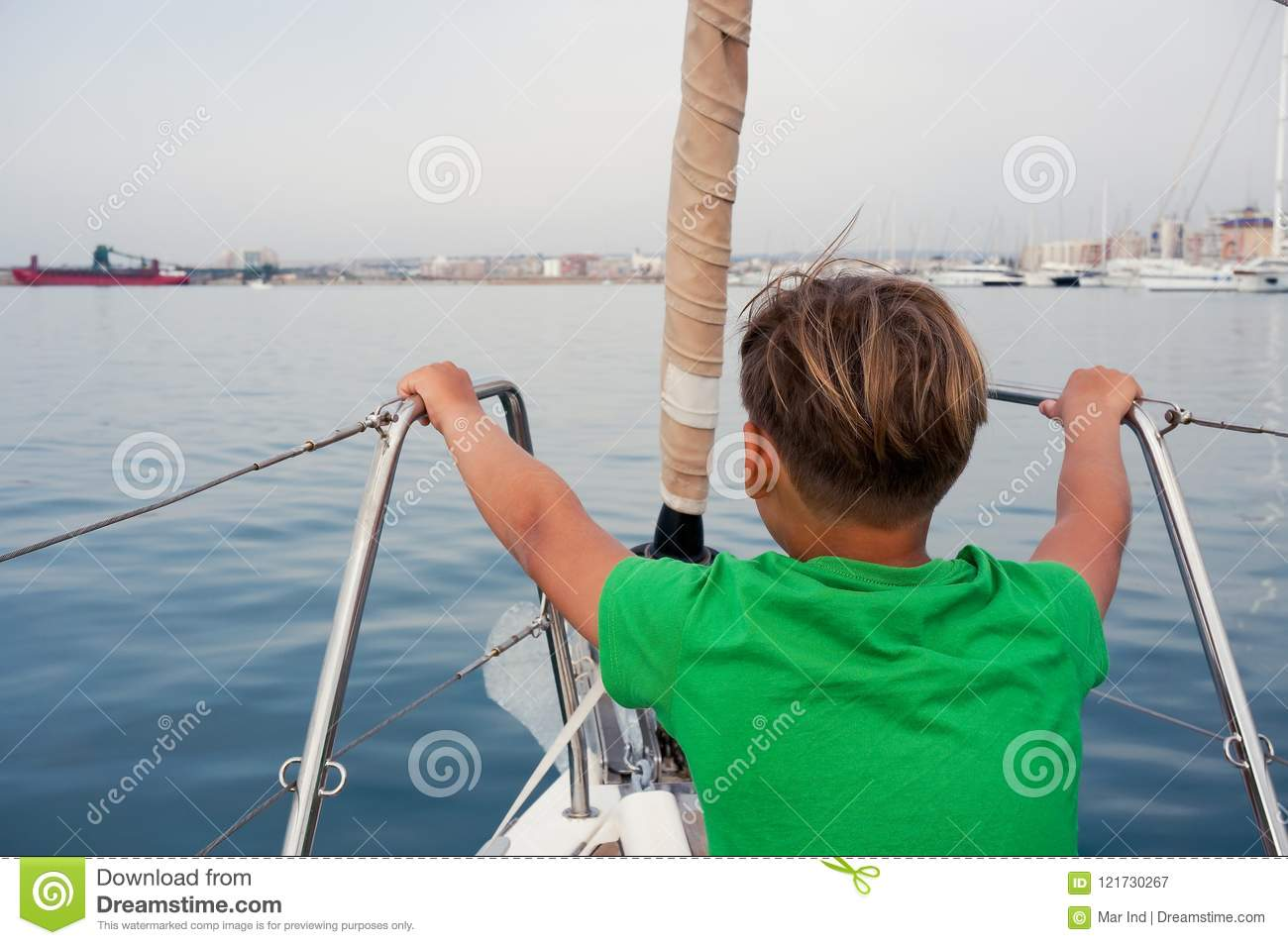 Boy sitting on yacht nose
