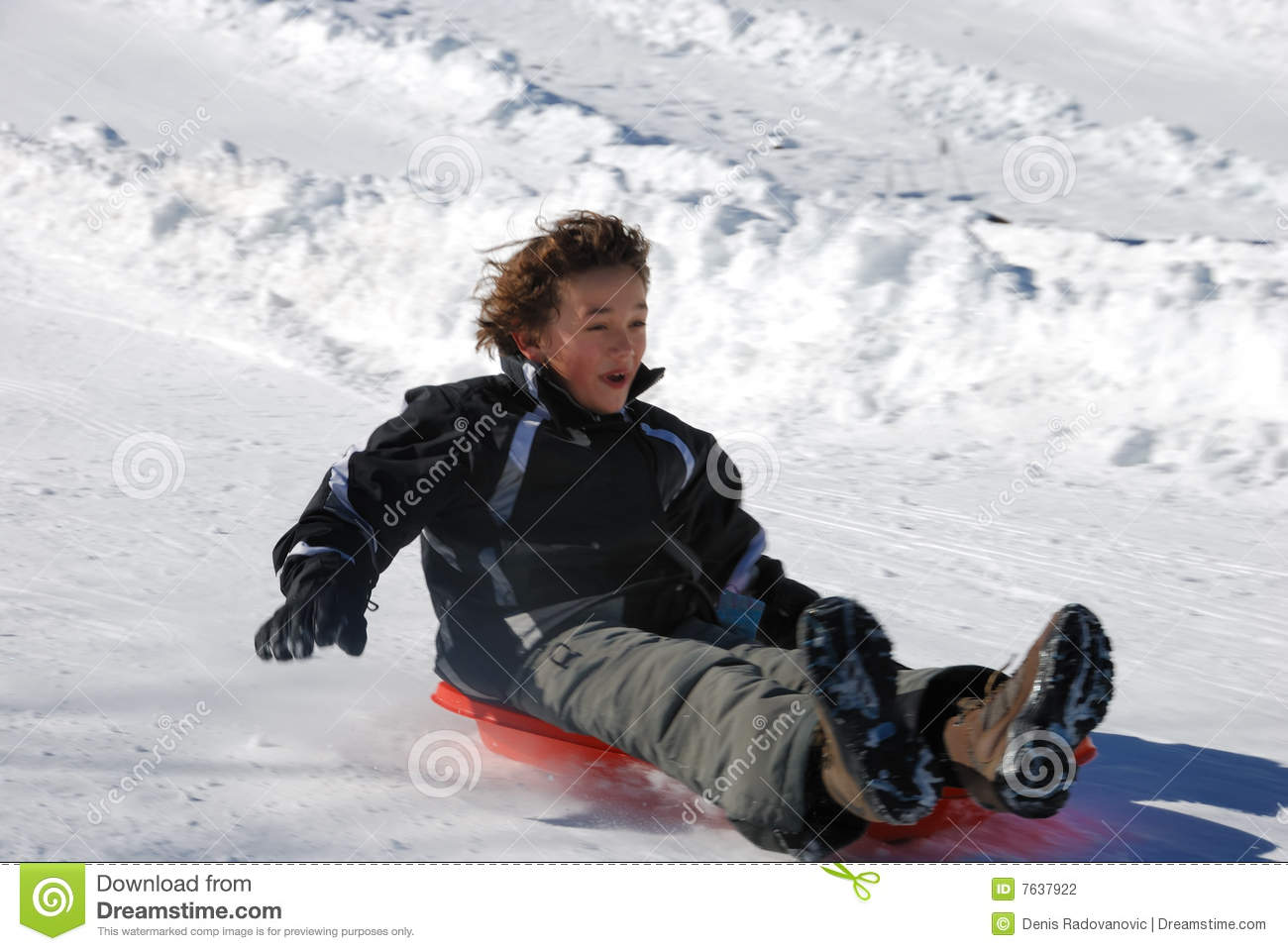 Boy Sledding Fast Down The Hill On A Red Sled Stock