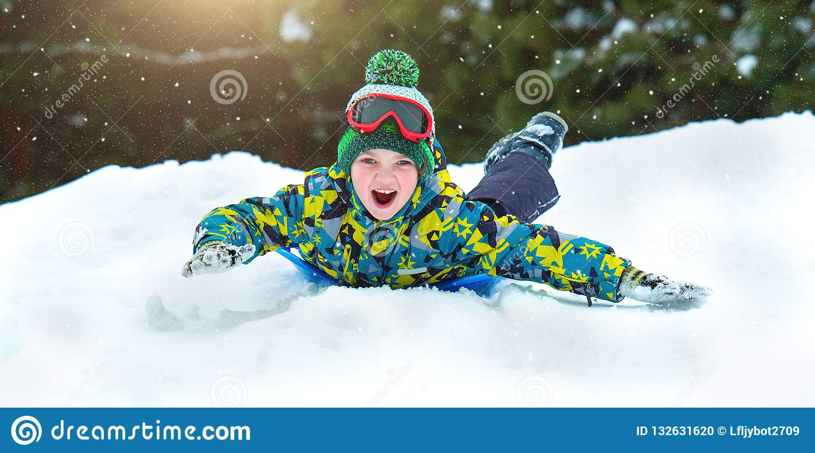 Boy sledding in a snowy forest. Outdoor winter fun for Christmas vacation.