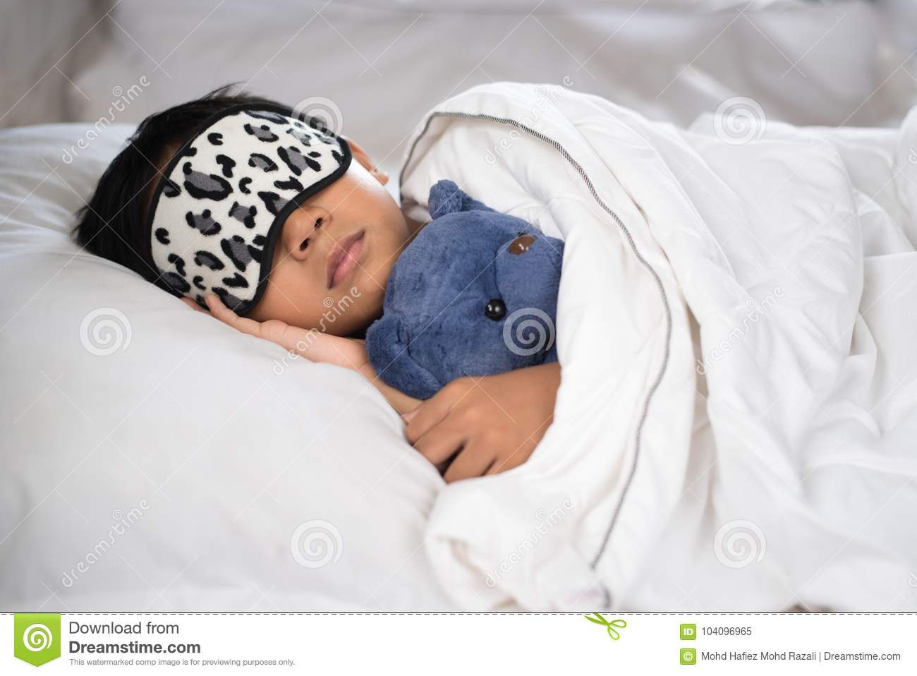 2d76615e8 Boy sleeping on bed with teddy bear white pillow and sheets wearing sleep  mask.boy fall asleep in morning.sleep concept
