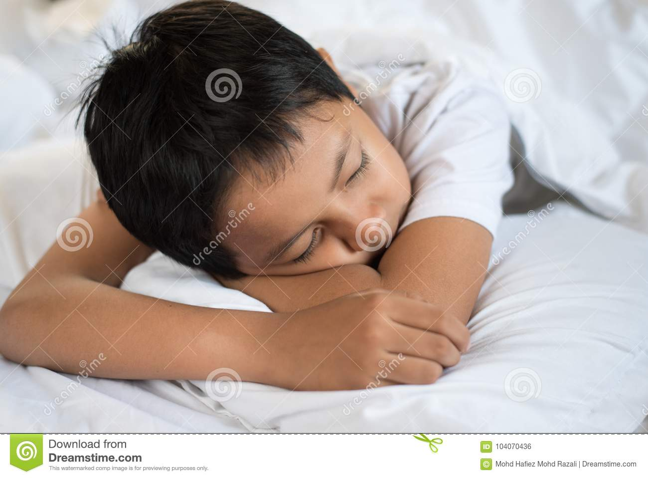 de097ab0d Boy sleeping on bed with white sheet and pillow.asian kid fall asleep  daydreaming.sleep concept