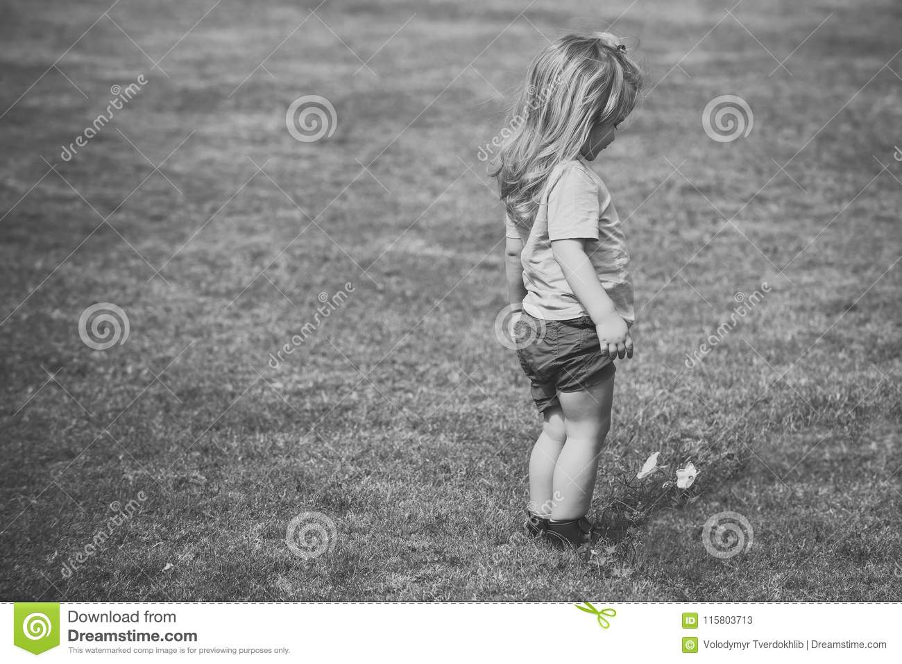 Small Boy With Long Blond Hair Looking At White Flower Stock Image
