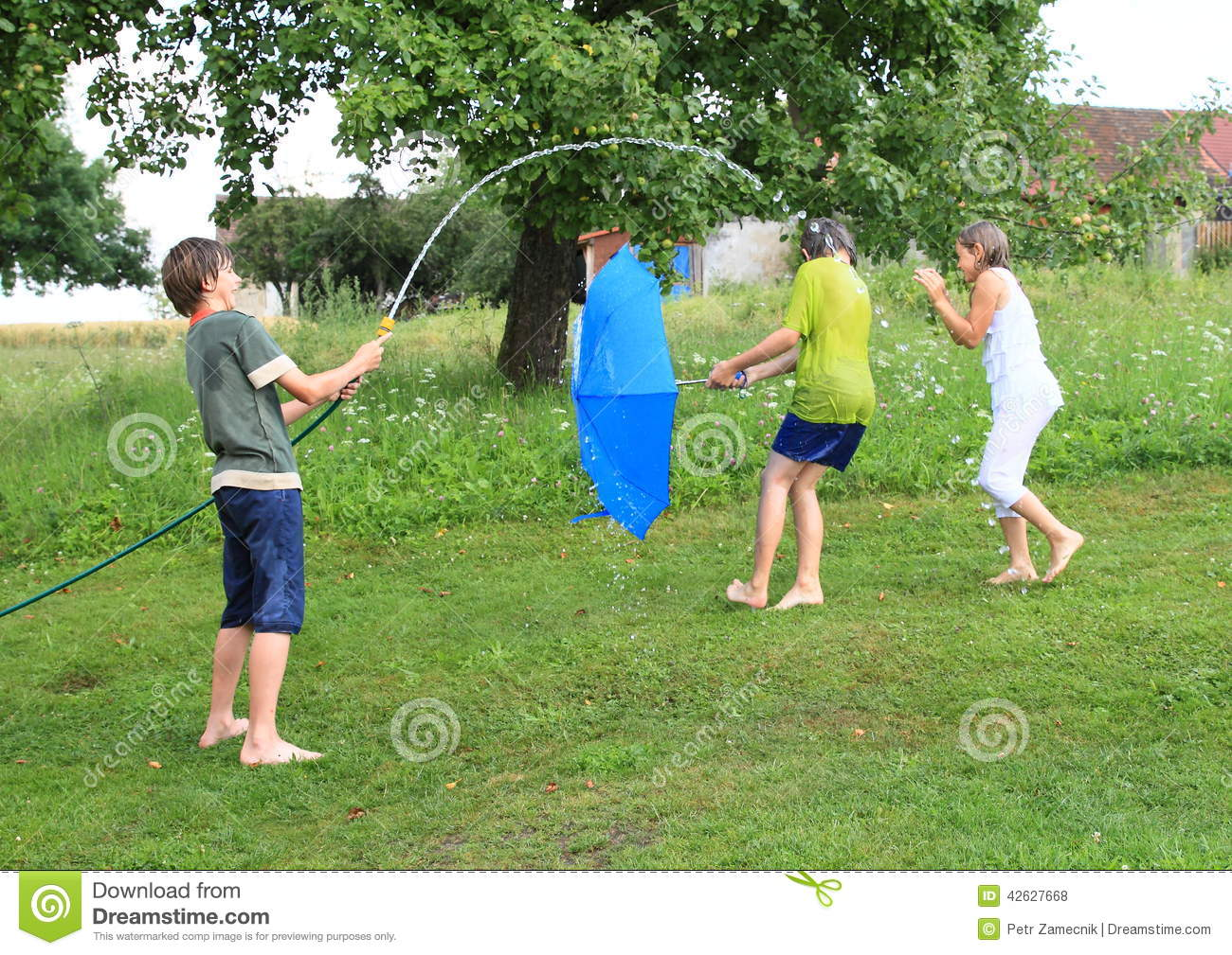 Boy splashing another kids with garden hose