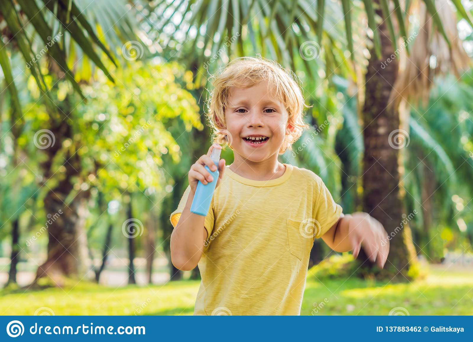 Boy spraying insect repellents on skin