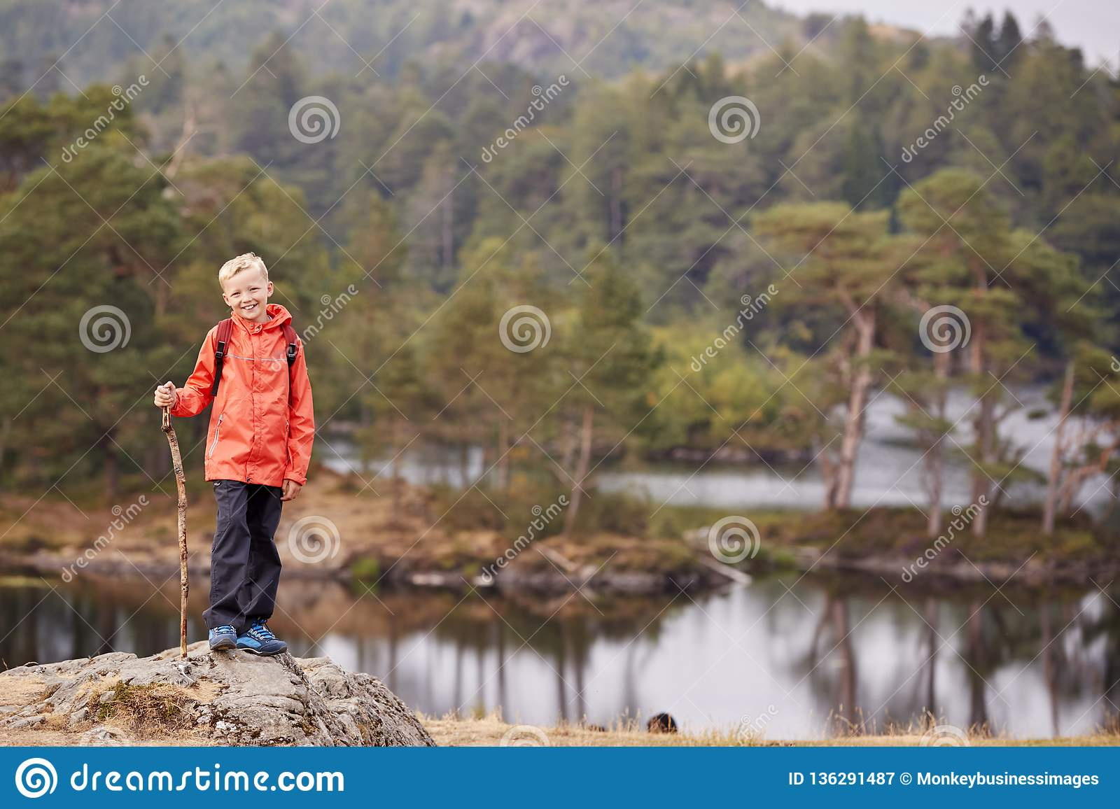 A boy standing on a rock by a lake holding a stick, smiling to camera, Lake District, UK