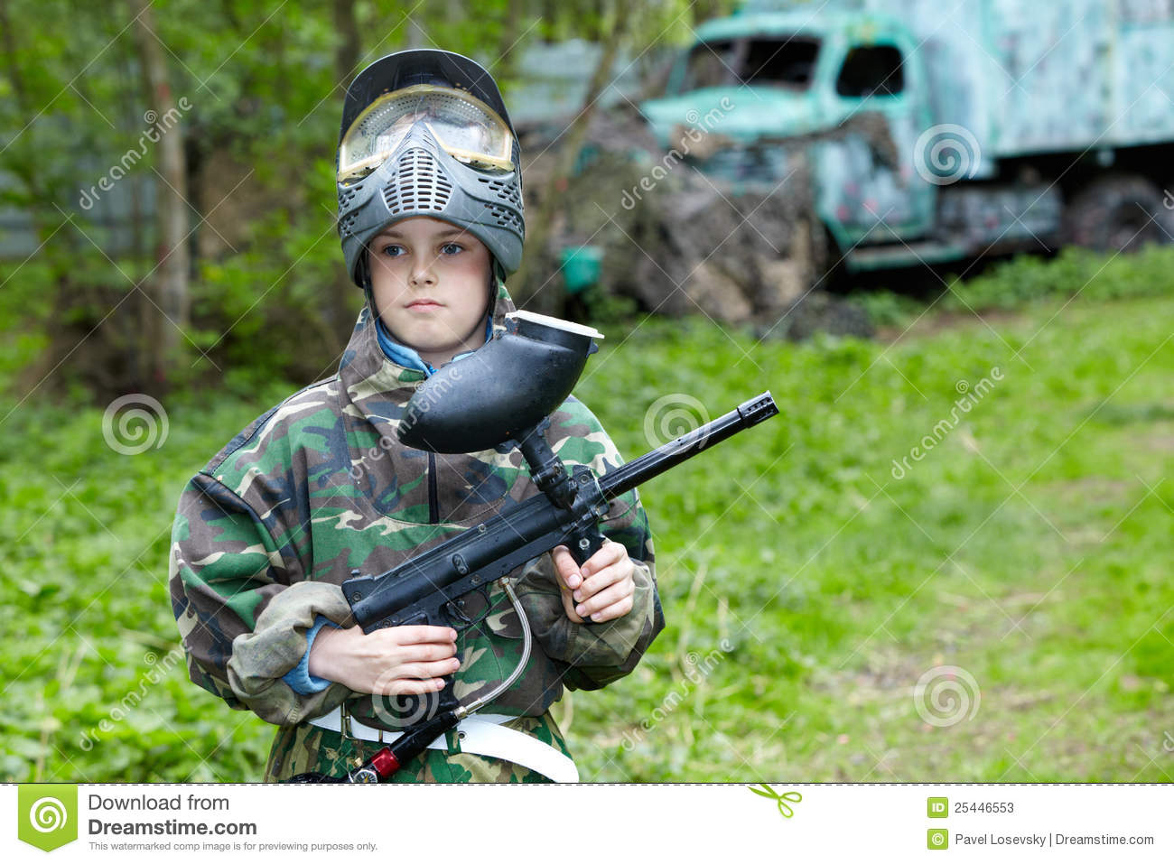 Boy stands against paintball area with old aba