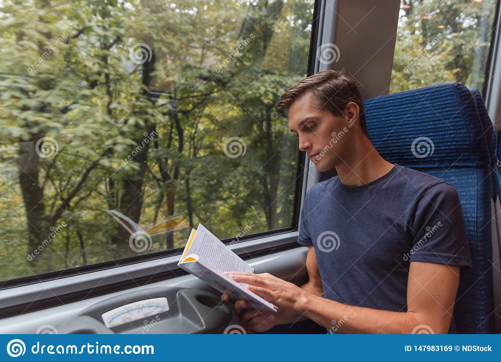 Young handsome man reading a book while travelling by train