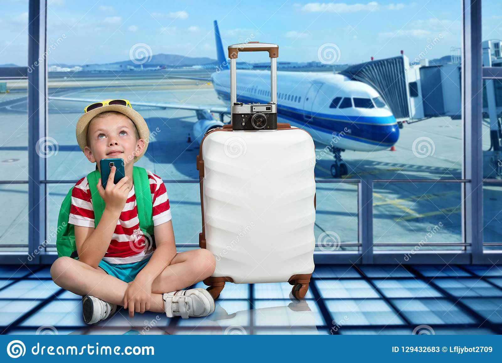 A boy with a suitcase sits at the airport and waits for landing on the plane.