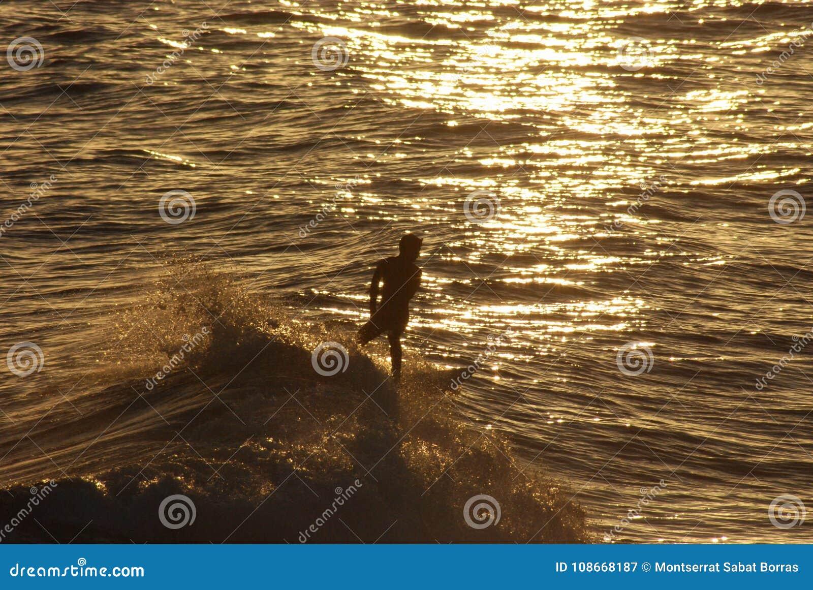Boy Surfing On A Mediterranean Beach At Sunset Stock Image