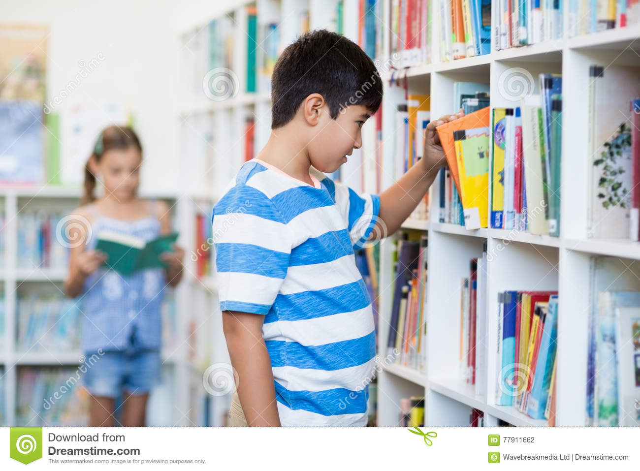 Boy Taking A Book From Bookshelf In Library
