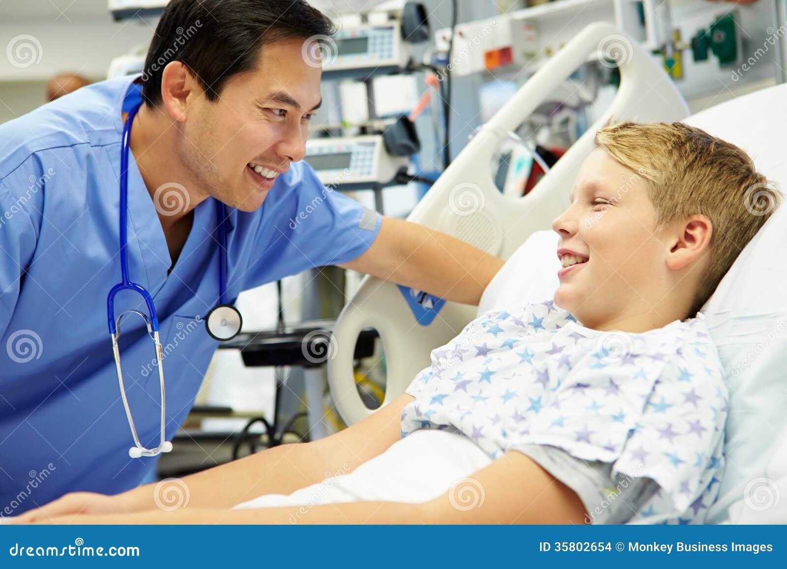 Boy Talking To Male Nurse In Emergency Room Stock Photo