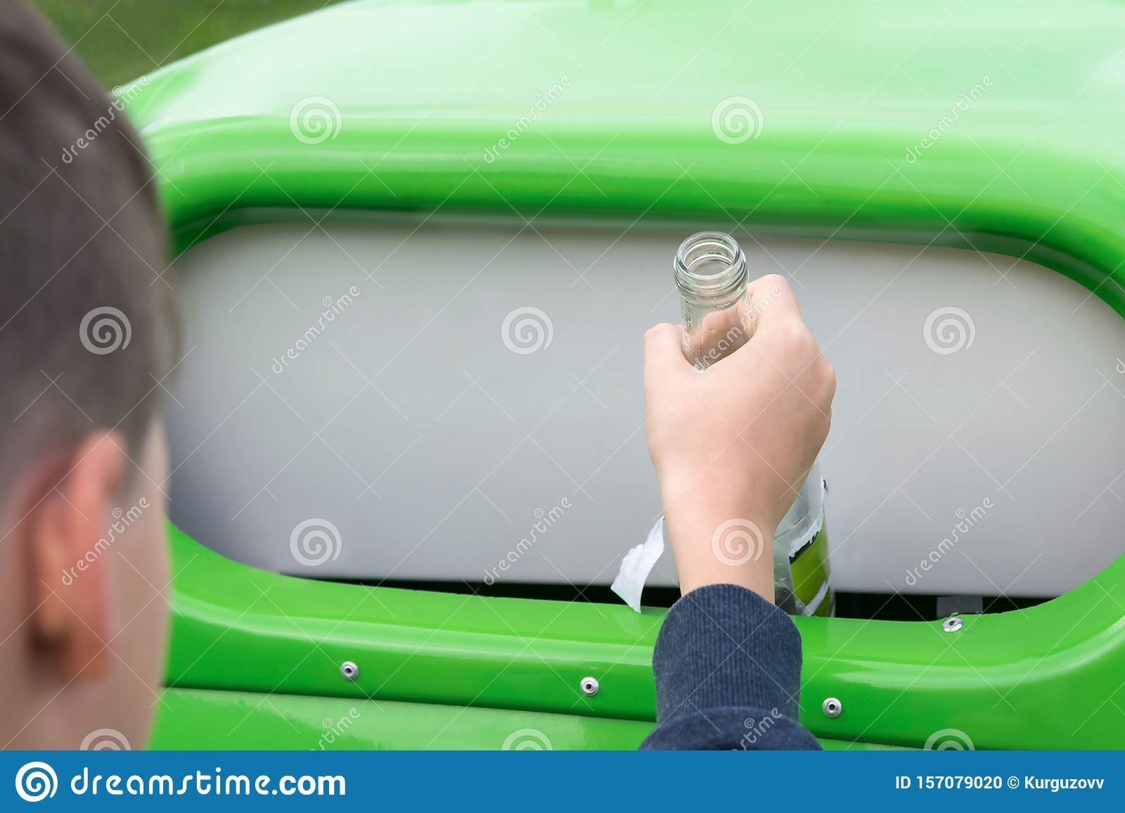 A boy throws an empty glass bottle into a special container for glass, close-up