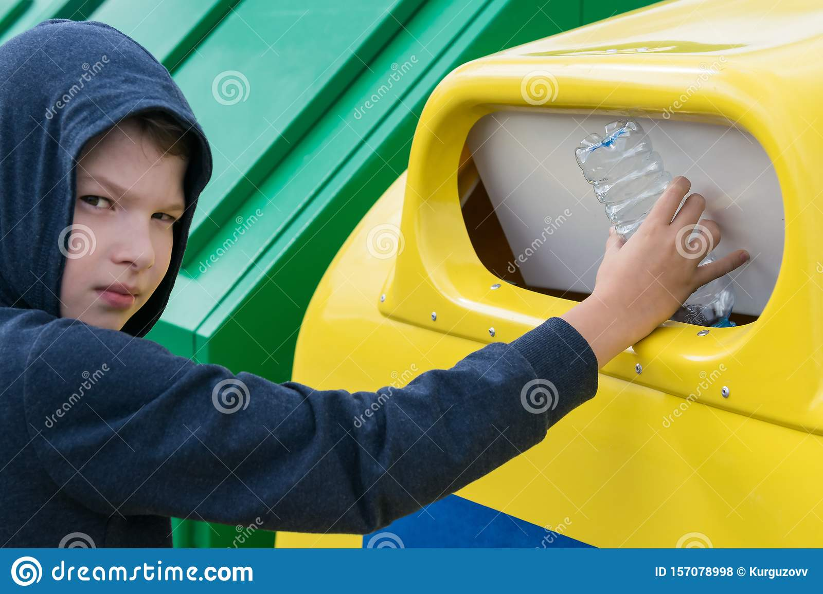 Boy throws an empty plastic bottle into a container for collecting separate garbage