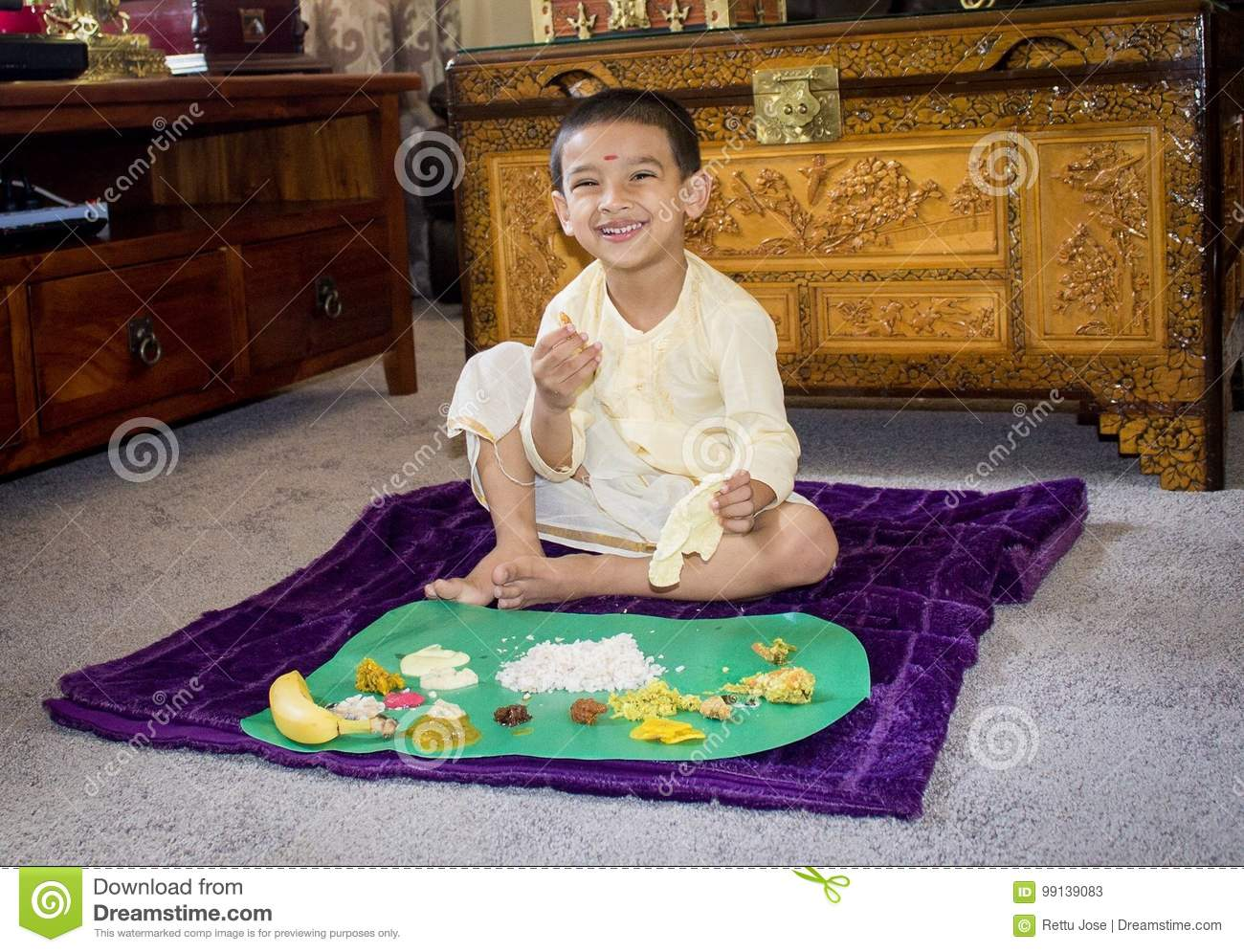 Boy with traditional clothes on onam day and having lunch