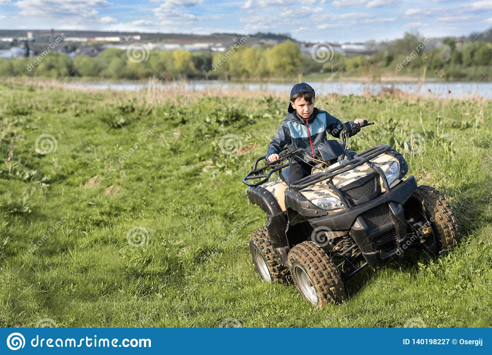 The boy is traveling on an ATV
