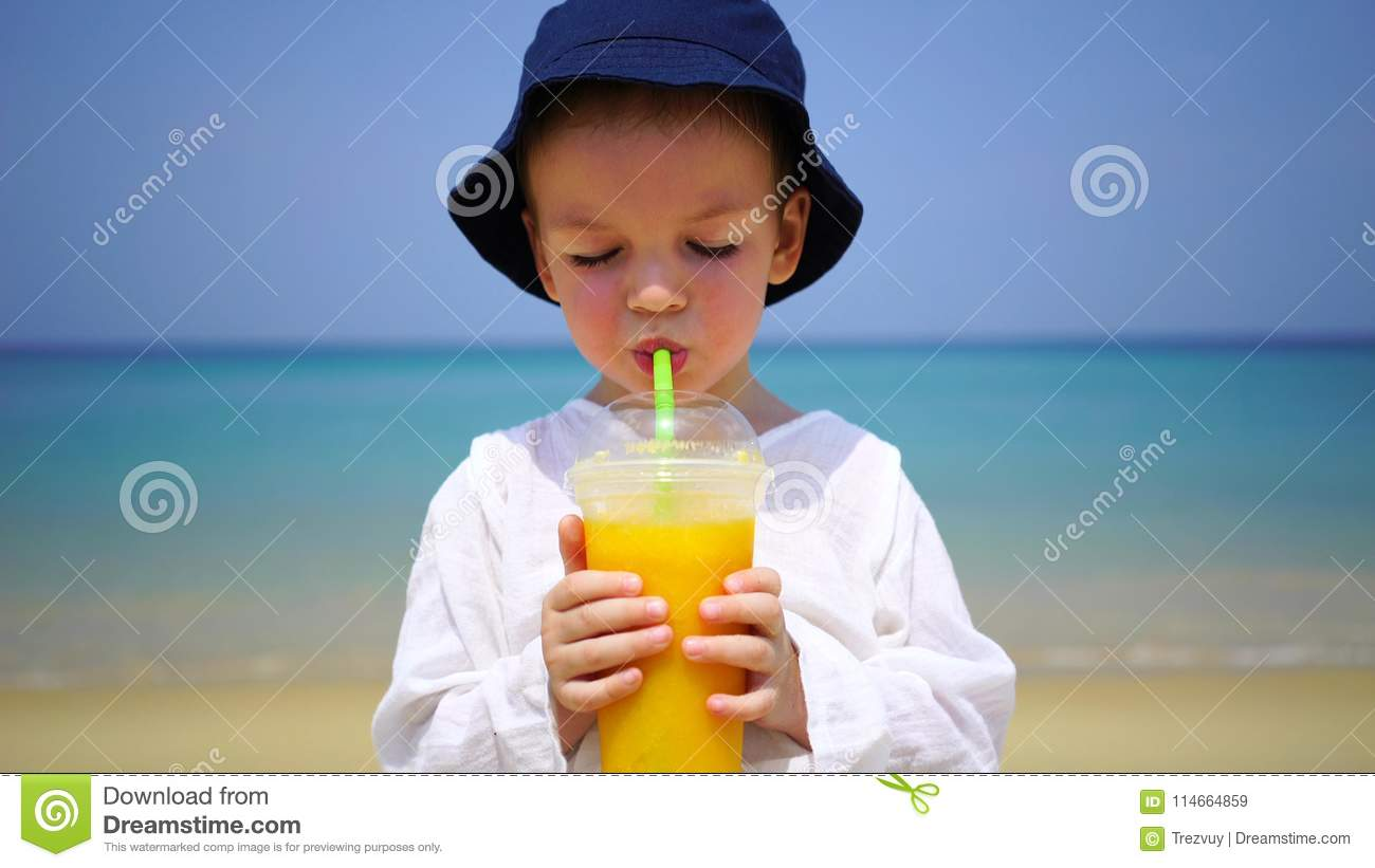 Boy of two years drinking mango fresh on the beach on the background of the ocean.