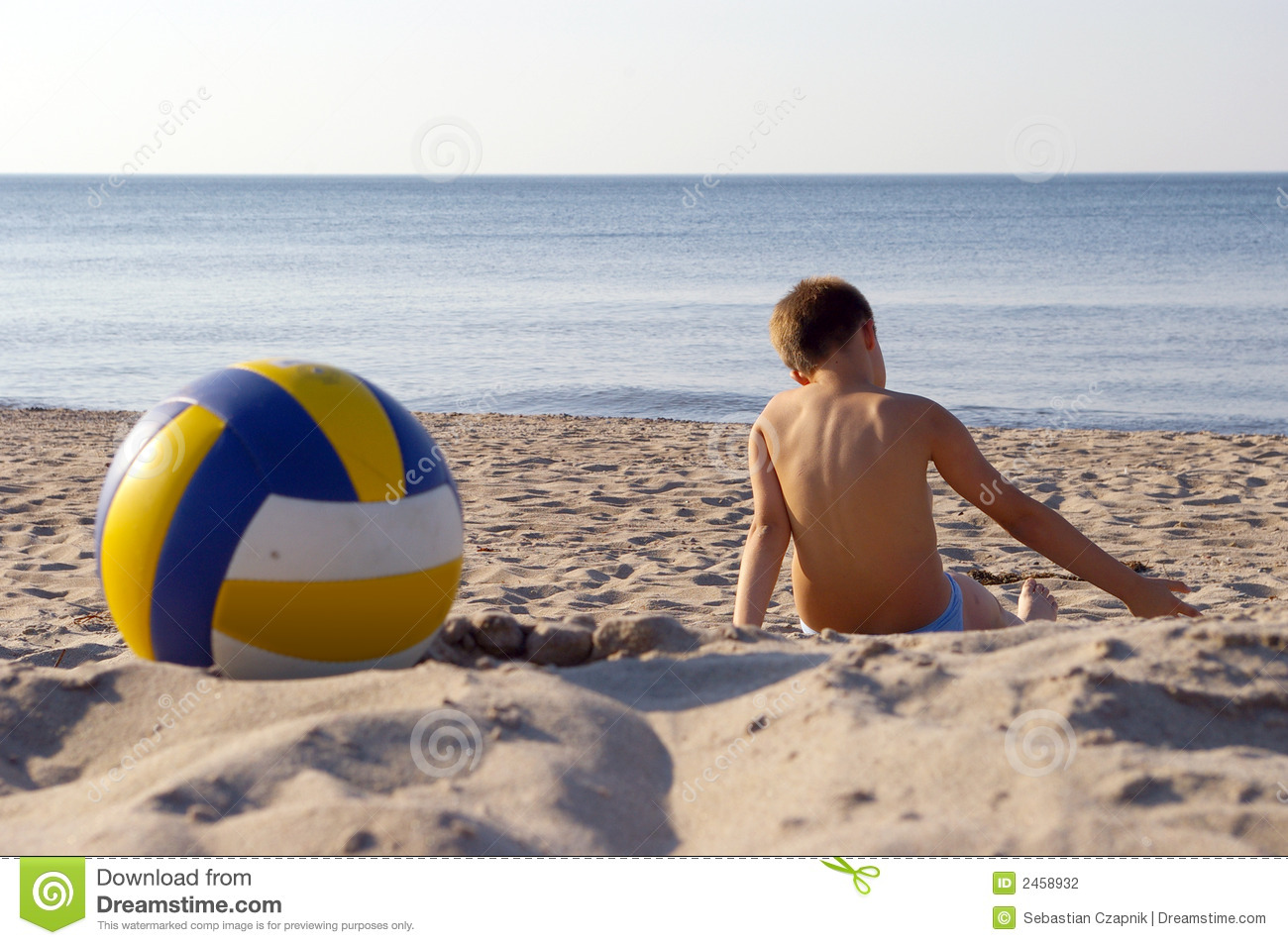 Boy with volleyball on beach.