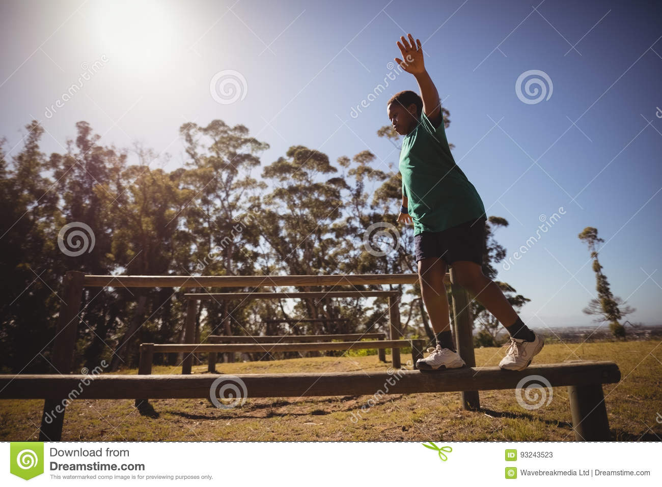Boy walking on obstacle during obstacle course