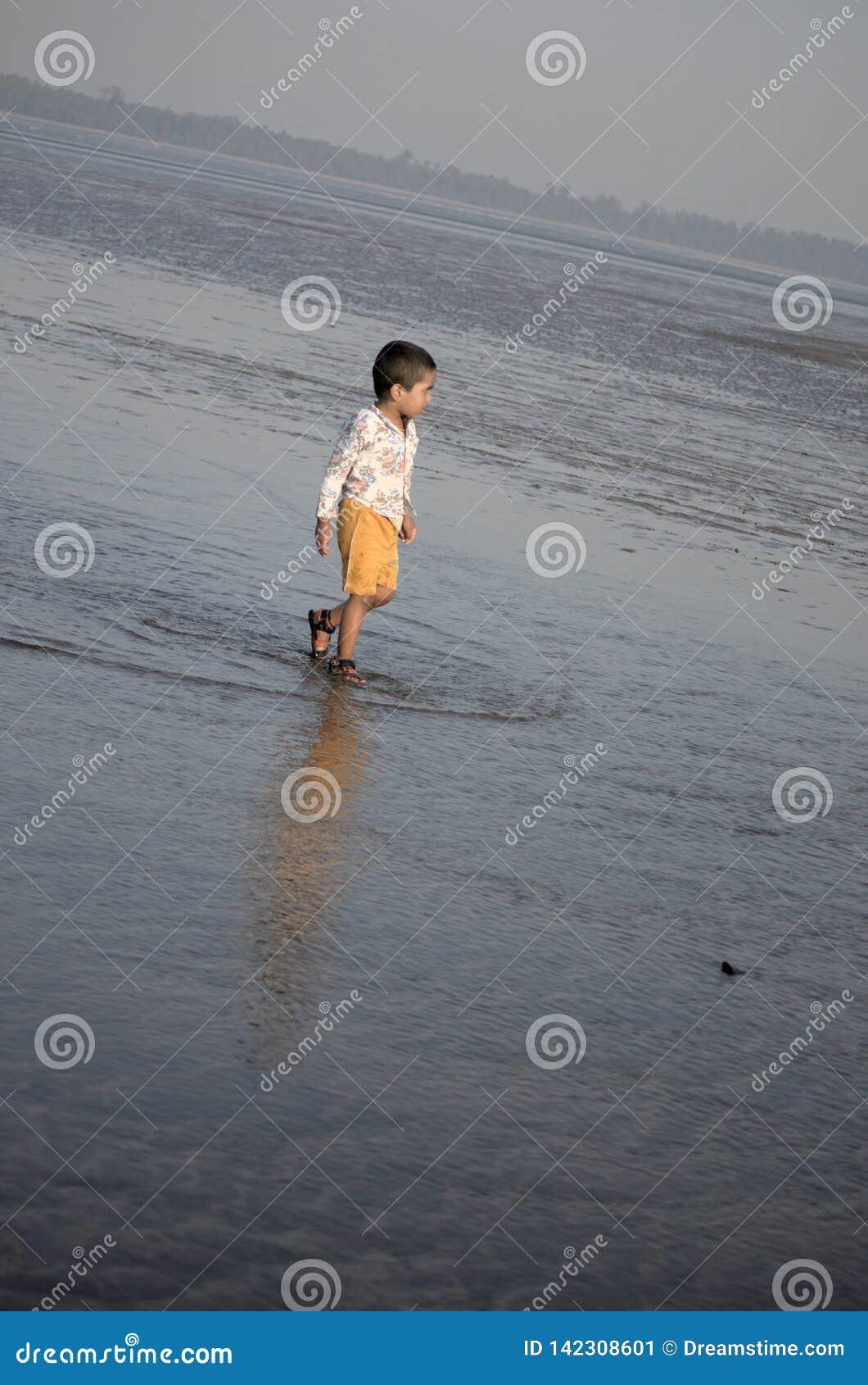 Boy walking in sea water