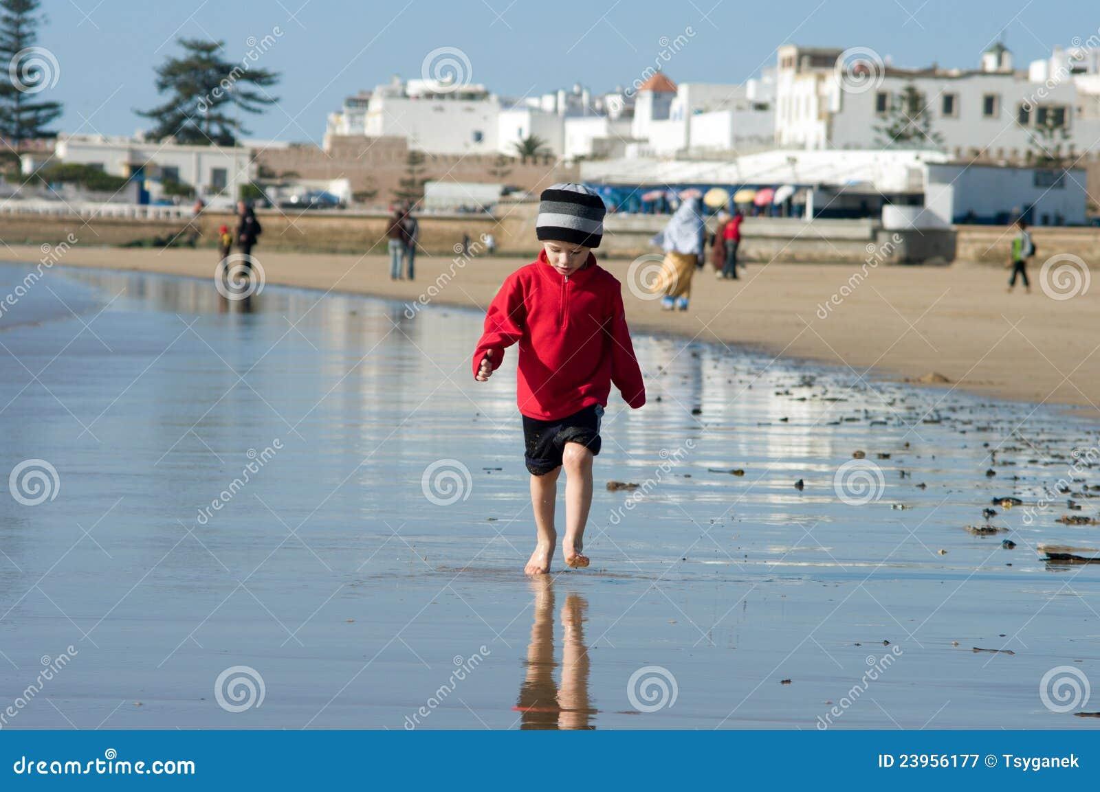 A boy walks on the ocean shore in Morocco
