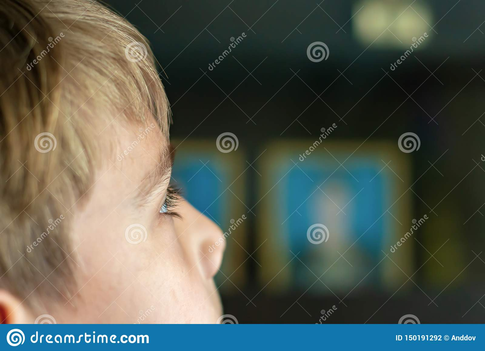The boy is watching TV, the child`s eyes are close up, against the background of a working television