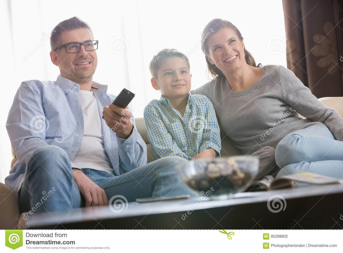 Boy watching TV with parents in living room