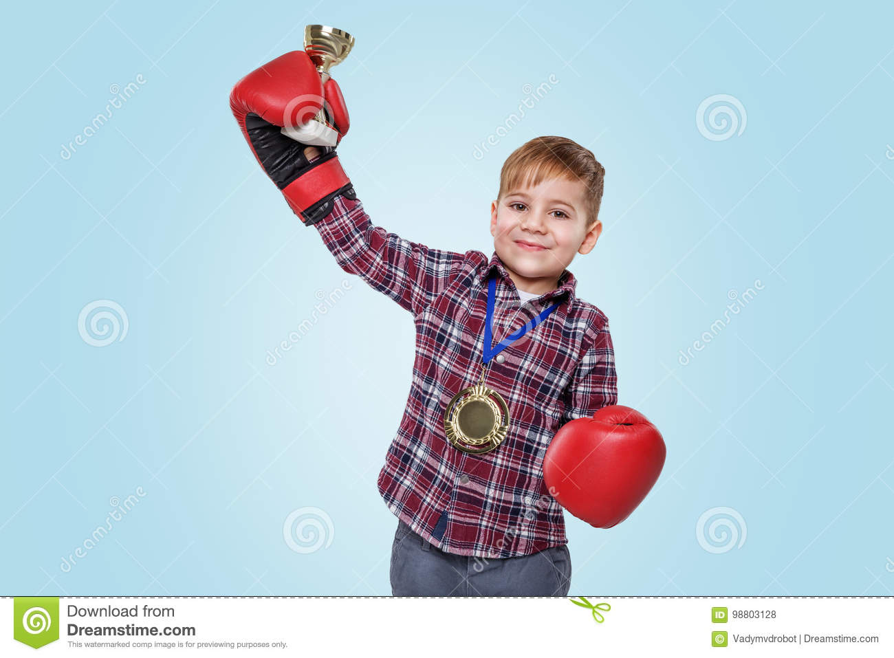 Boy wearing boxing gloves and celebrating success with golden trophy