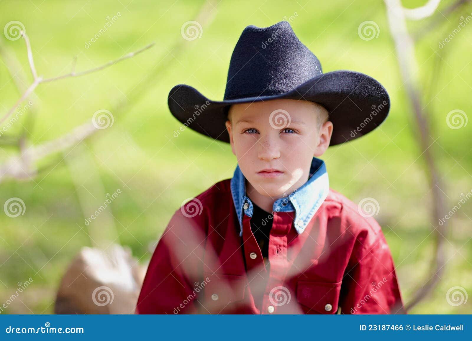 Portrait of a young boy wearing a black cowboy hat. a5e3e8212cf