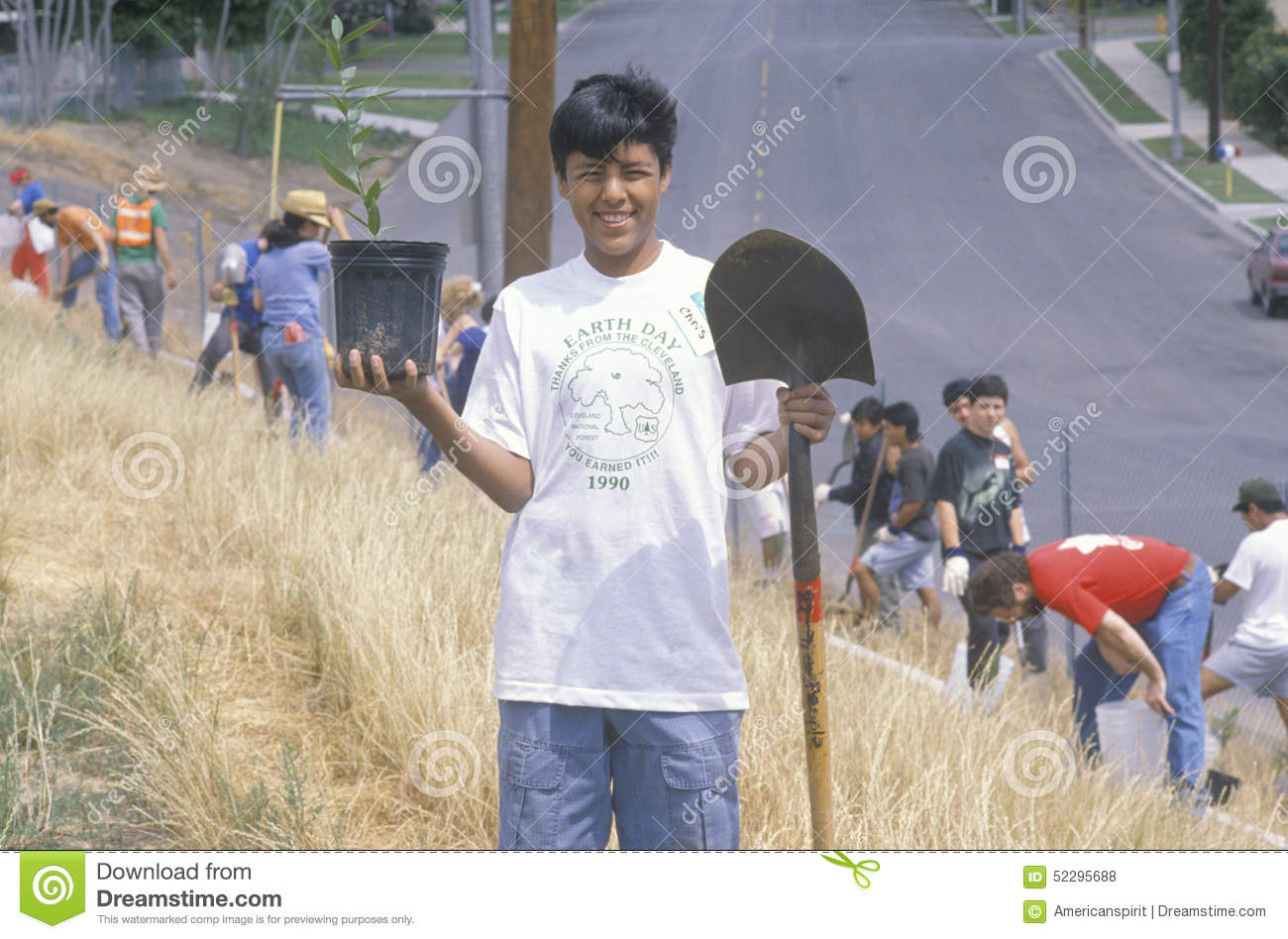 A boy wearing an Earth Day t-shirt participating in a tree planting by the Clean & Green volunteers of the Los Angeles