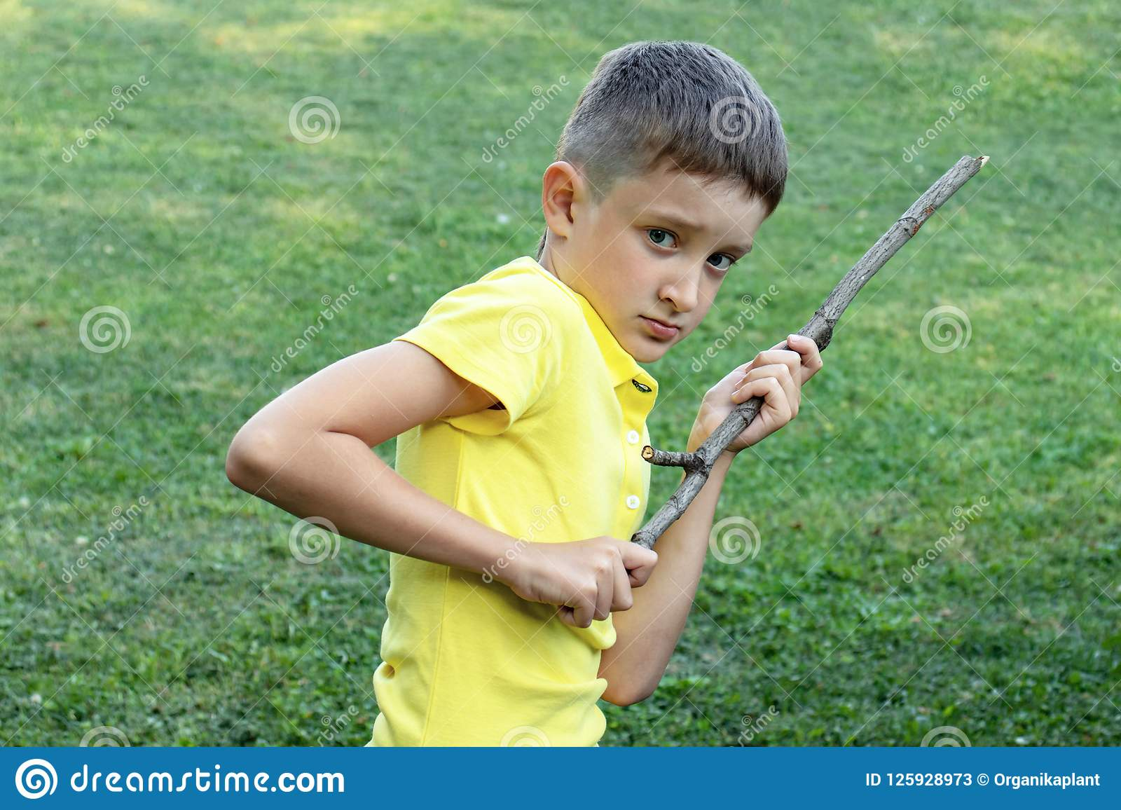 A boy witn angry face holding a stick in his hands