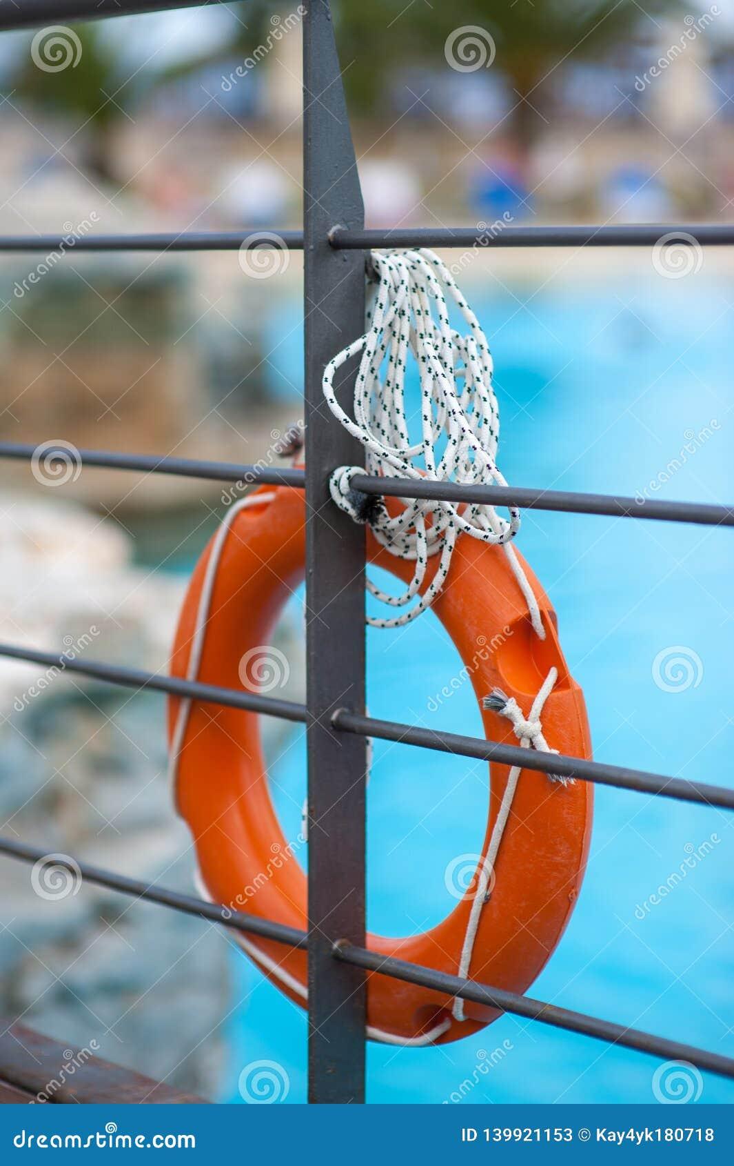 Boya de vida anaranjada con la cuerda cerca de la piscina que cuelga en el puente