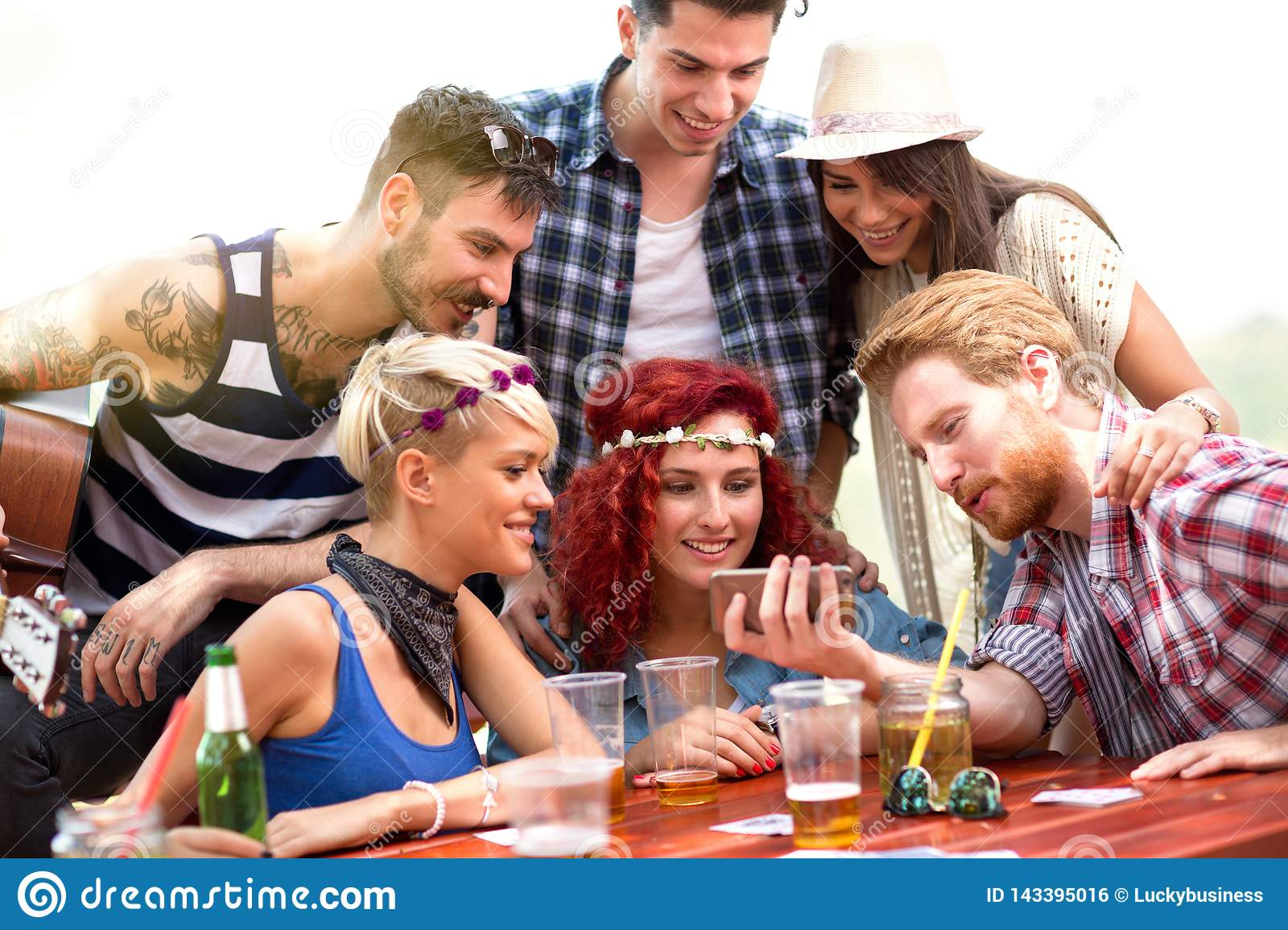 Boys and girls on picnic in nature having fun while watching photos on mobile phone