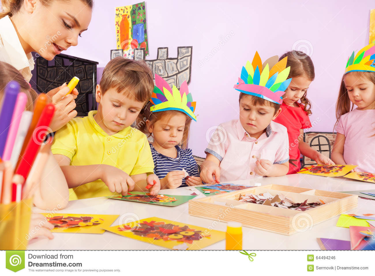 Boys girls and teacher glue paper to cardboard stock for Craft classes for toddlers