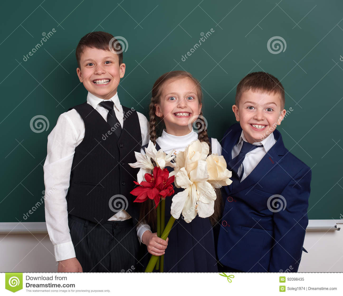 Boys giving girl flowers, elementary school child near blank chalkboard background, dressed in classic black suit, group pupil, ed