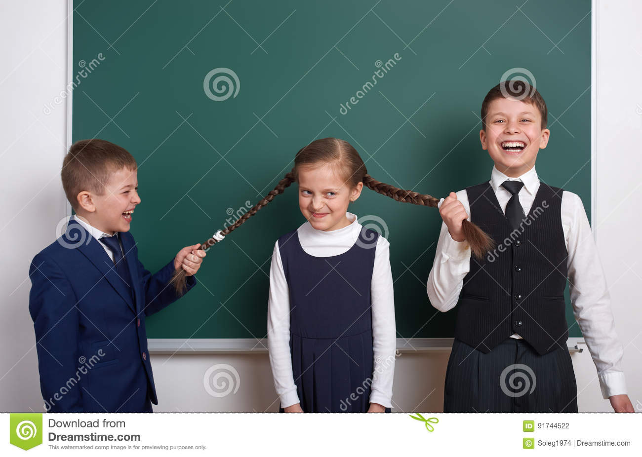 Boys pull the girl braids, elementary school boy near blank chalkboard background, dressed in classic black suit, group pupil, edu