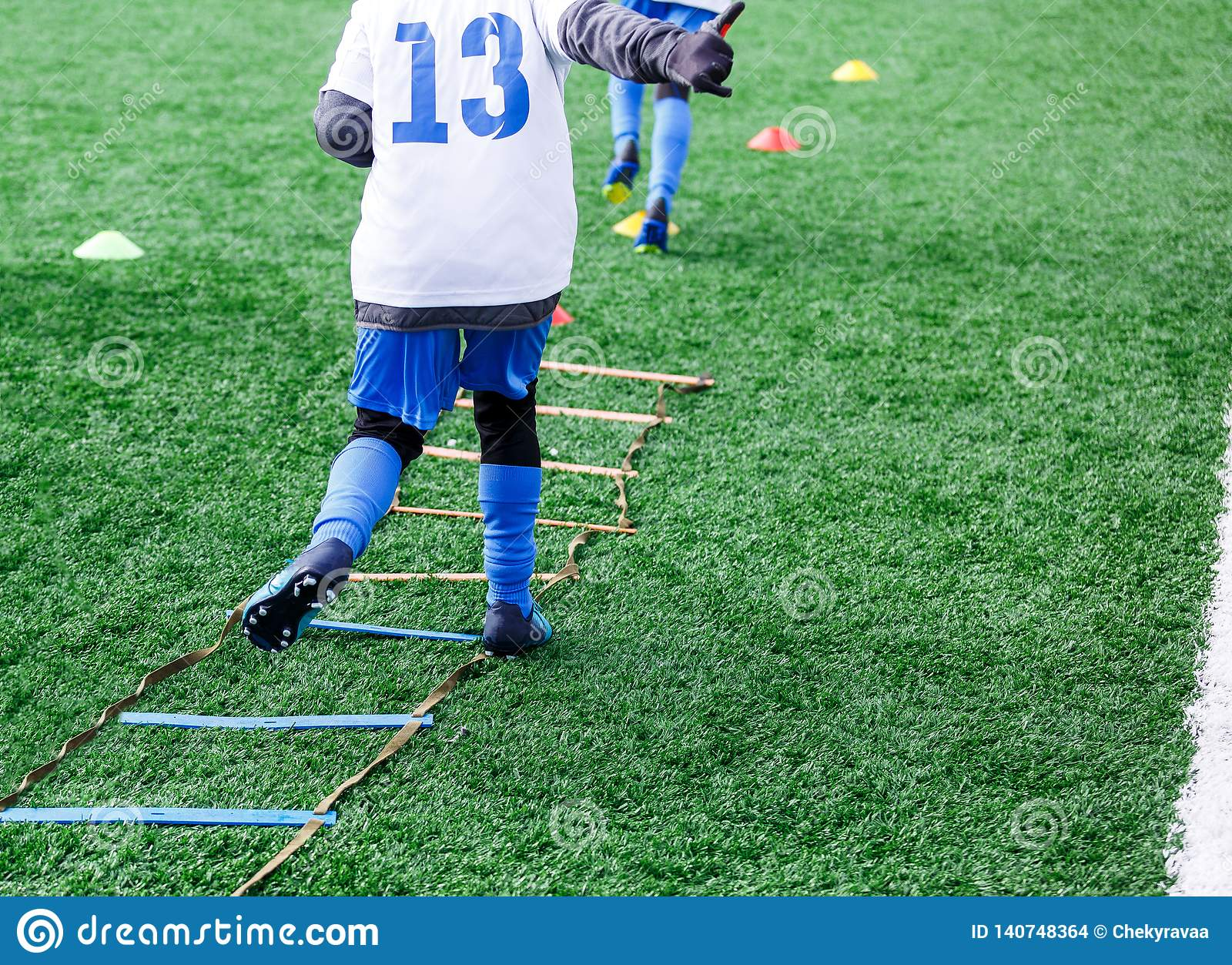 Boys in white and blue football sport form make exercises on green field. Football for children, active lifestyle. Training