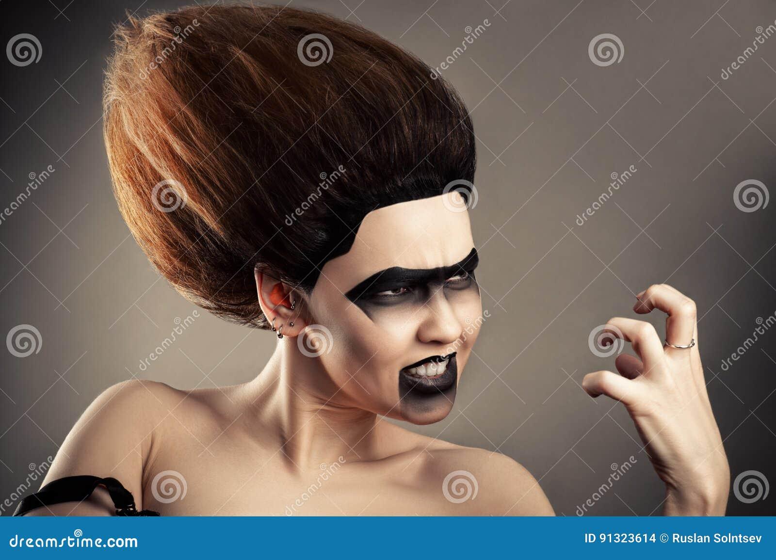 Boze donkerbruine vrouw met donkere make-up en weelderig kapsel