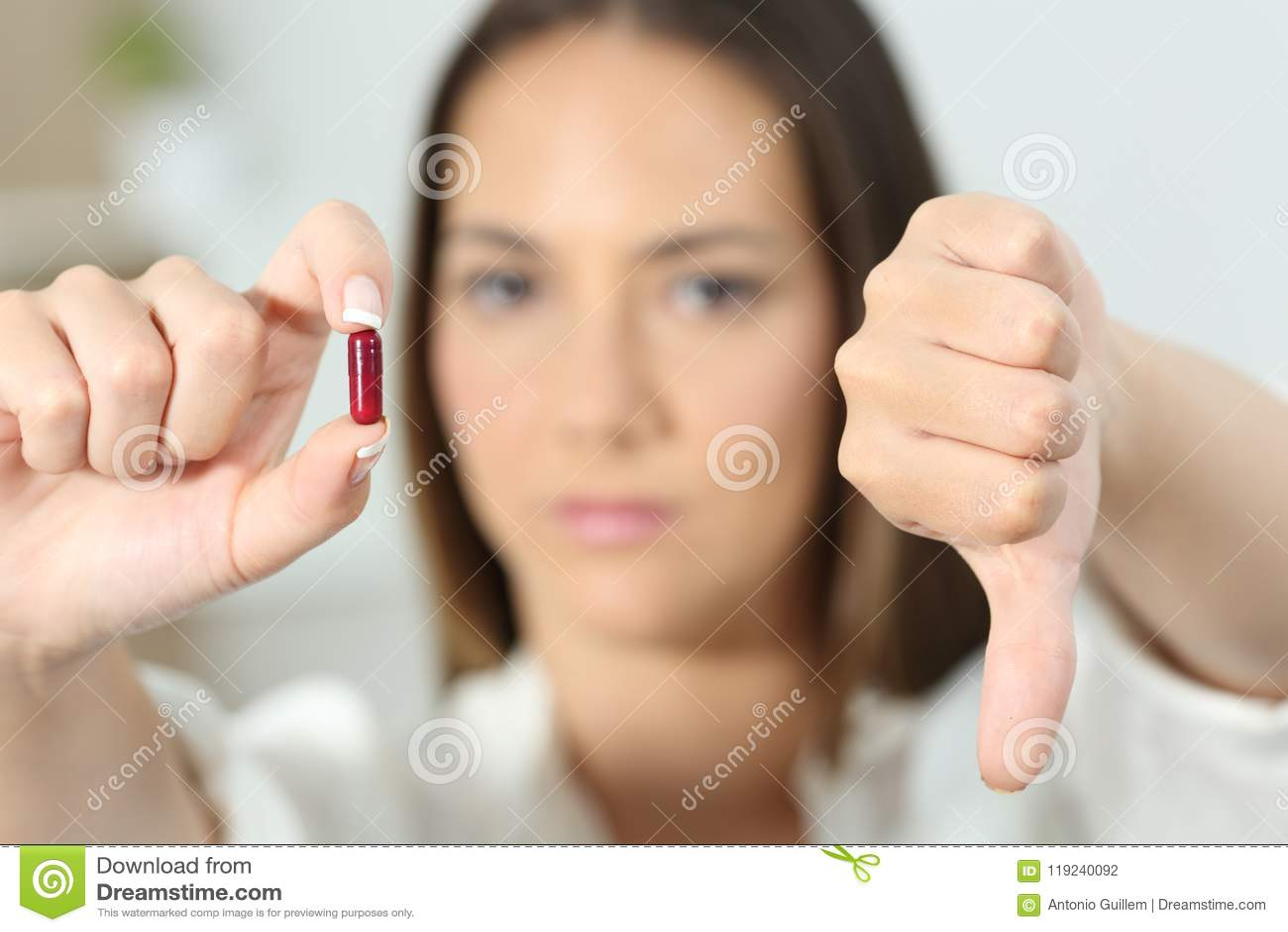 Boze vrouwenhand die pil met neer duimen tonen