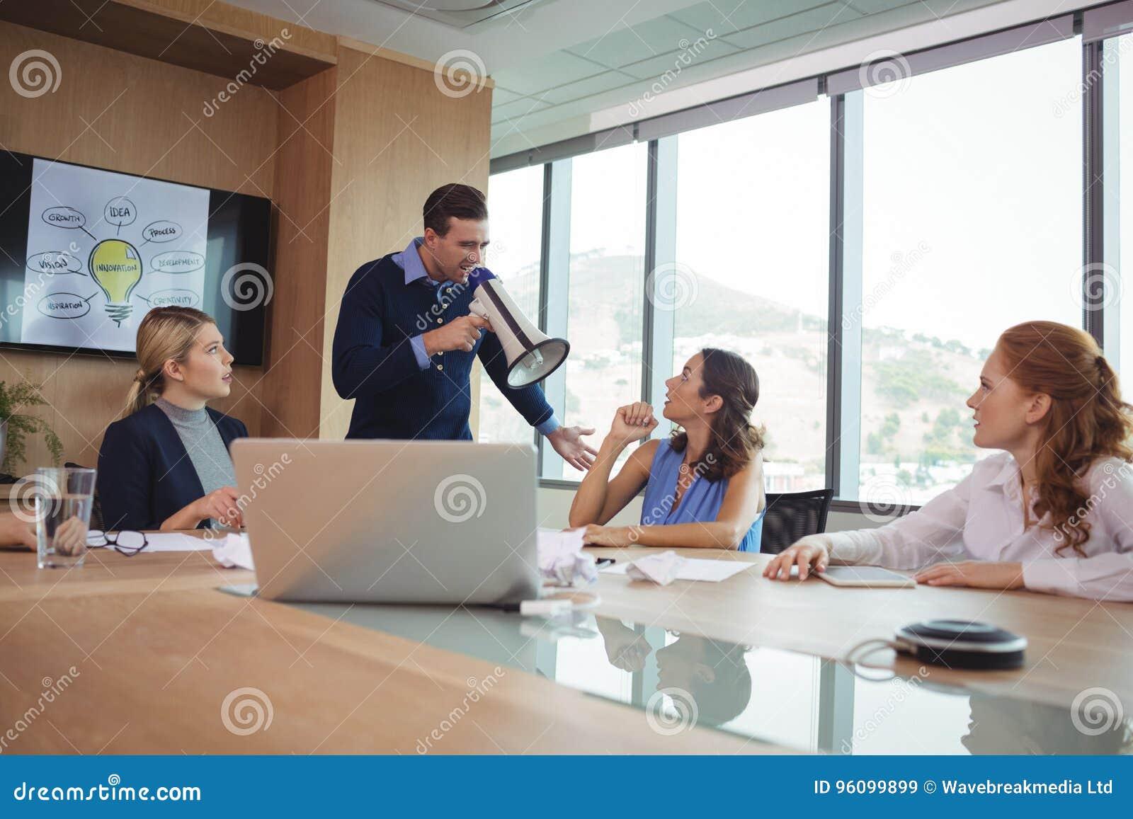 Boze zakenman die megafoon in conferentieruimte met behulp van