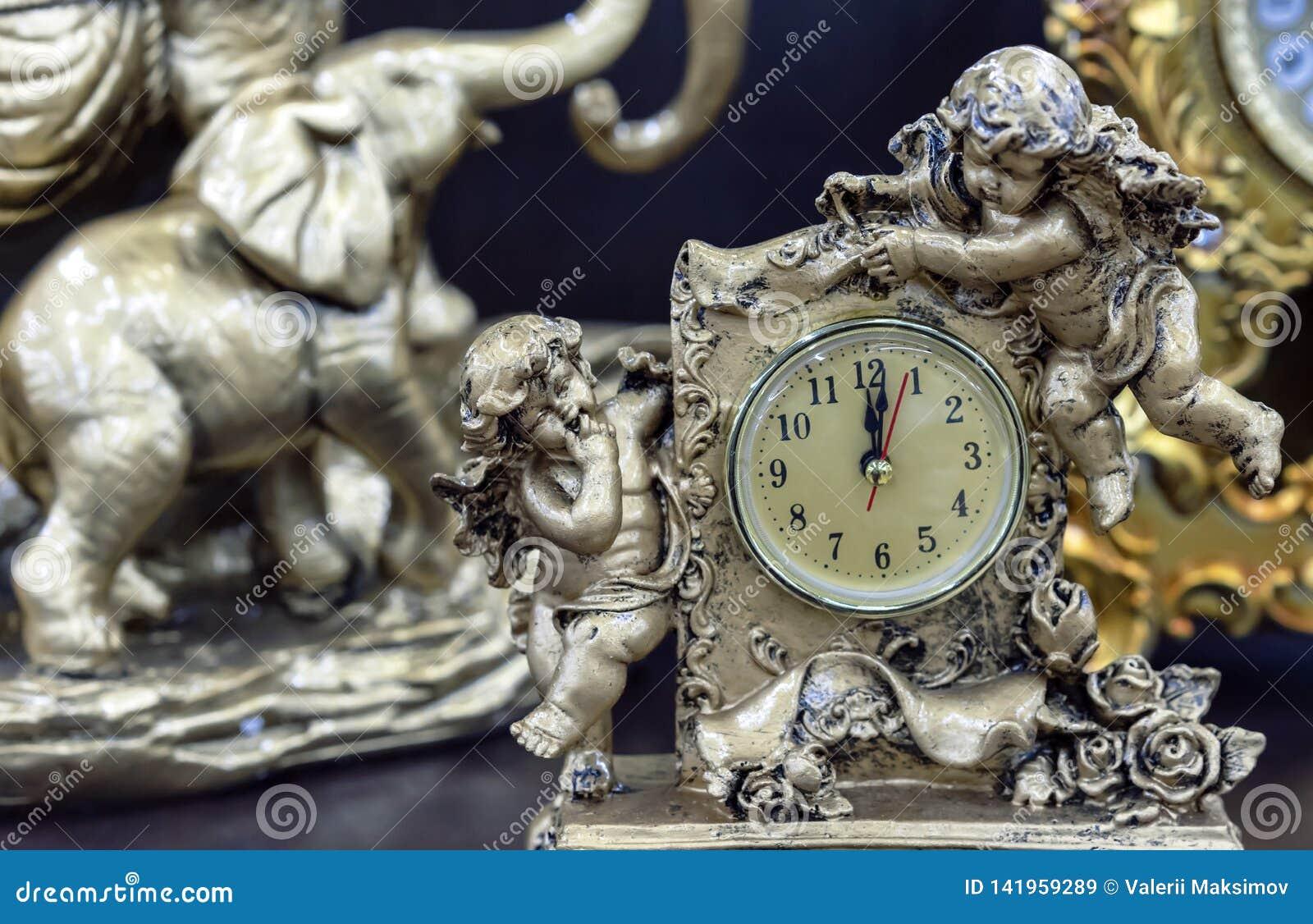 Brązowy stołowy zegar z aniołami na drewnianym stole