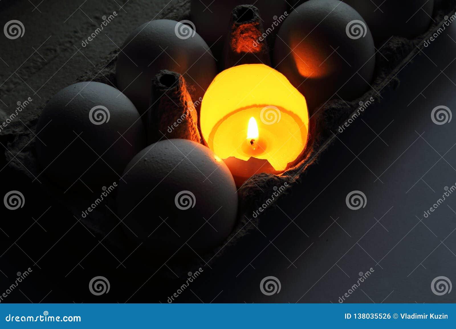 Brännande stearinljus i äggskal som symbol av liv bland ägg i kartong målat gräs för 2 placerade allt för easter för hinkfågelung