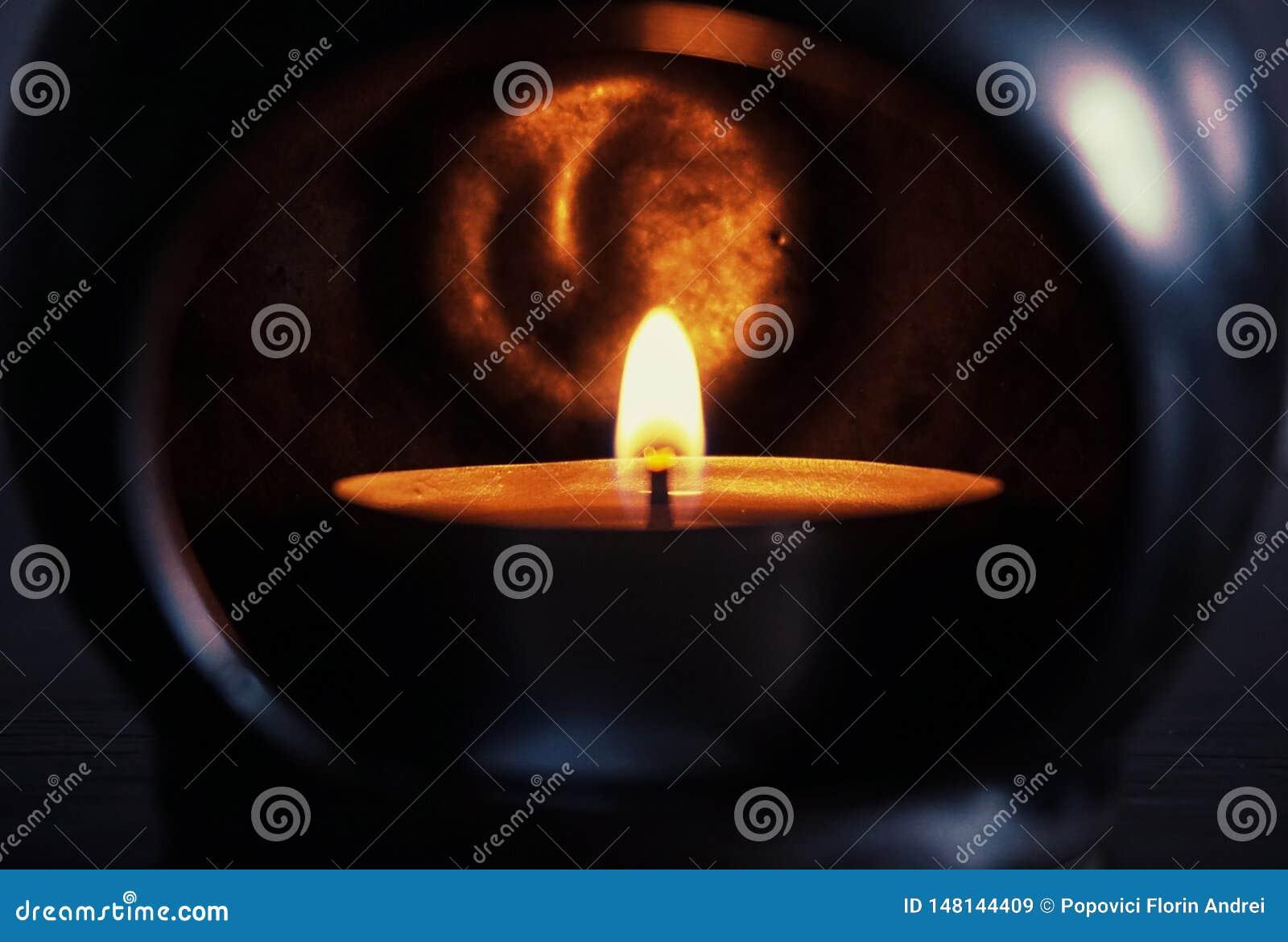 Brännande stearinljus i ett mörkt ställe