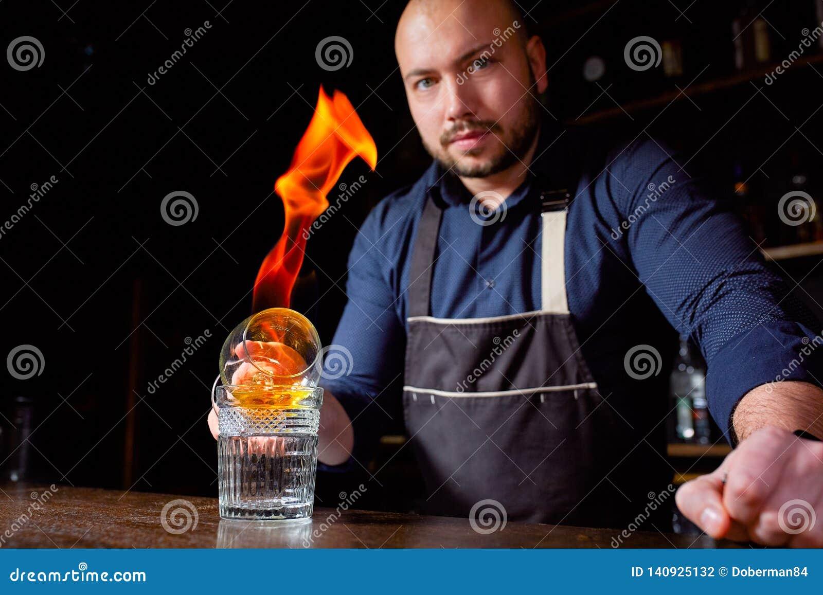 Brännhet show på stången Bartendern gör den varma alkoholiserade coctailen och antänder stången Bartendern förbereder en brännhet